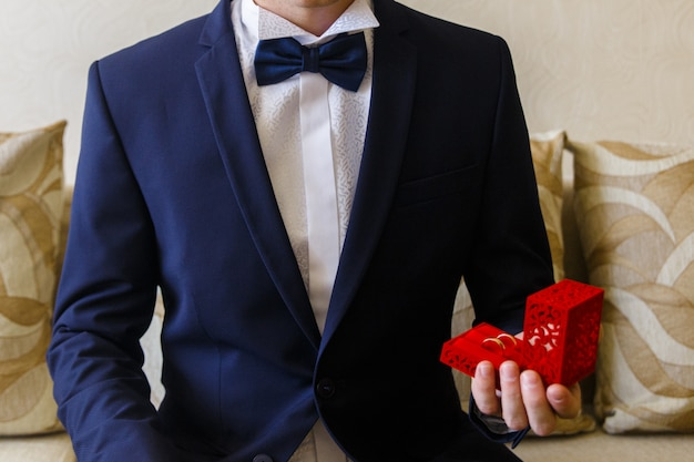 Man in the blue suit holds little gift-box with wedding rings