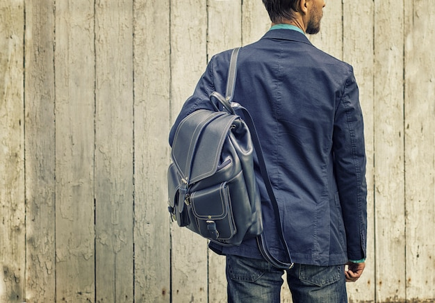 Man in blue suit and jeans with leather backpack