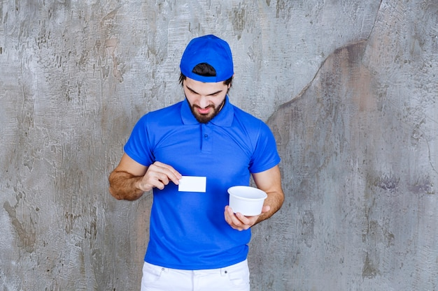 Man in blue uniform holding a takeaway plastic cup and presenting his business card.
