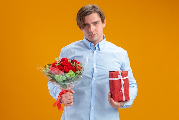 Man in blueshirt holding bouquet of red roses and present looking at camera smiling confident valentines day concept standing over orange wall
