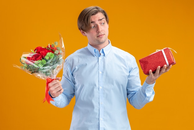 Man in blueshirt holding bouquet of red roses and present looking confused having doubts valentines day concept standing over orange wall