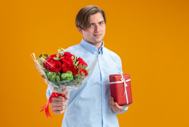 Man in blueshirt holding bouquet of red roses and present smiling confident valentines day concept standing over orange wall