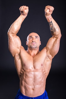 Man bodybuilder is demonstrating his perfect muscular.