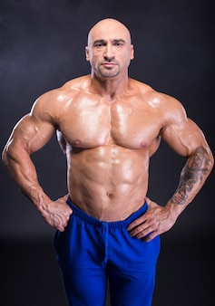 Man bodybuilder is demonstrating his perfect musculature
