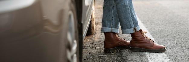 Uomo con gli stivali accanto alla macchina durante un viaggio su strada