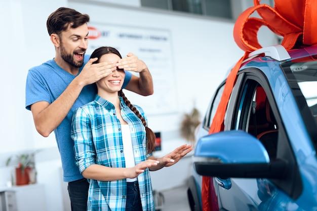남자는 젊은 아내를 위해 새 차를 샀습니다.