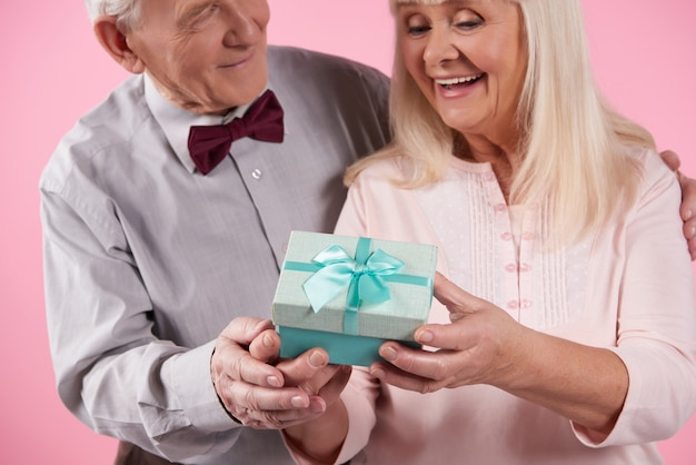 Man in bow tie presents gift box to beautiful woman.