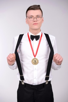 Man in bow tie and suspenders showing a gold medal.
