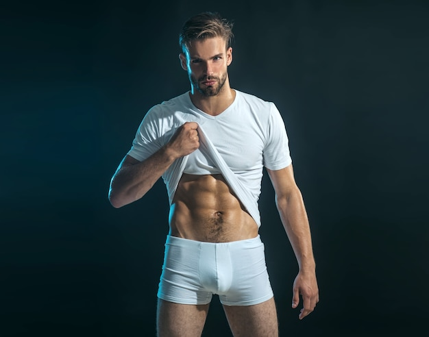 Man in boxer shorts shows abdominal muscles. muscular sexy man in white t-shirt which shows pres.