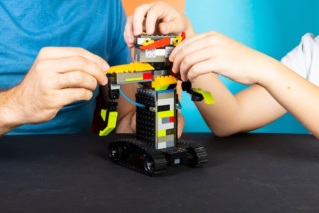 A man and a boy assemble from a constructor of a robot. male and children's hands collect lego