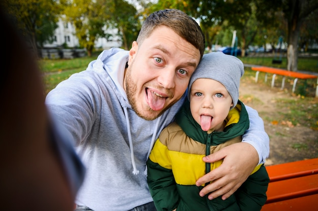 Man and boy taking a selfie with tongues out