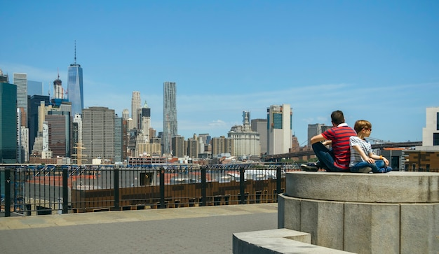 Man and boy with sunglasses sitting in front of manhattan skyline, in new york city