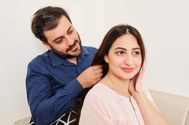 Man braiding hair of girlfriend