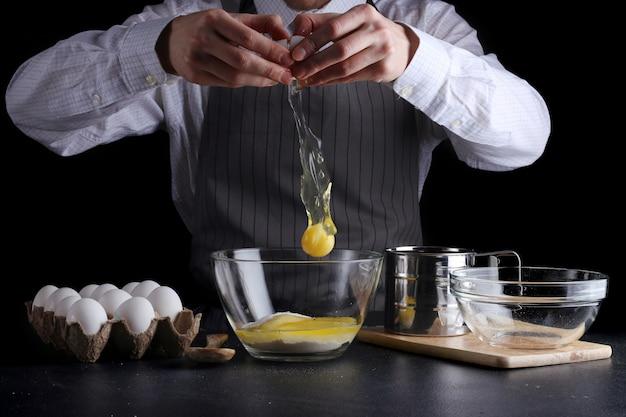 Человек, разбивающий яйцо в миске, готовит печенье