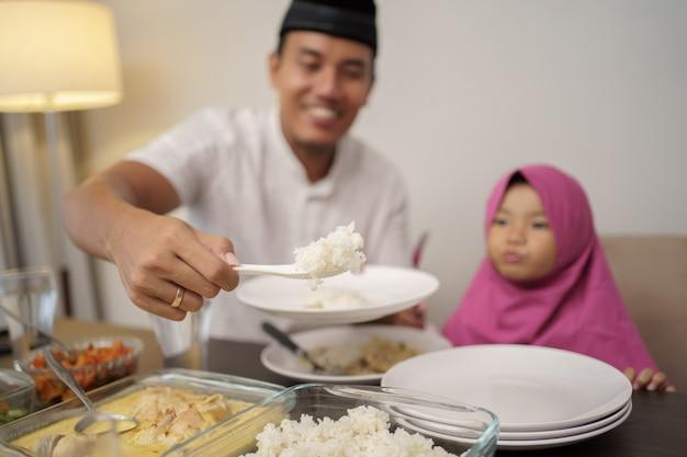 Человек разрывает быстрый обед со своей дочерью и семьей
