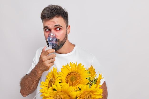 男は酸素マスクを通して呼吸しますひまわりにアレルギーがあります赤い涙目は目をそらします白の干し草熱のポーズに苦しんでいます