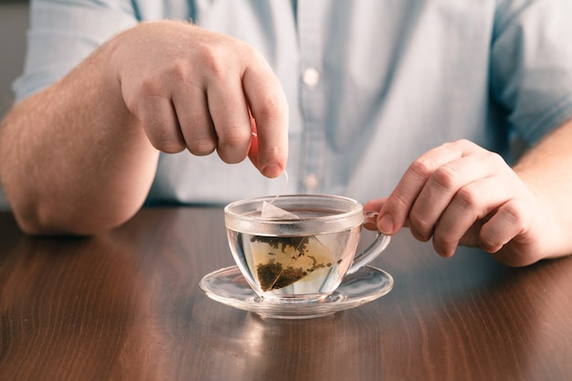 Man brewing tea bag with glass of tea on table in office