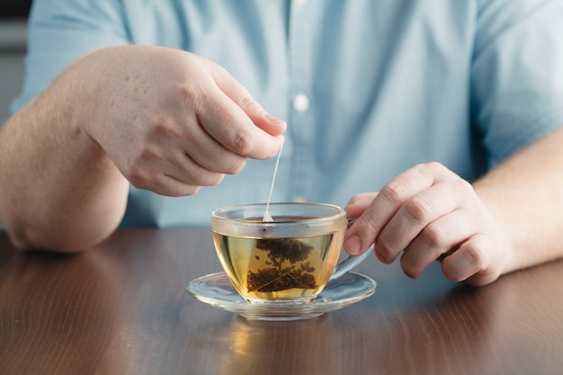 Man brewing tea bag with glass of tea on table