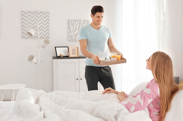 Man bringing breakfast to his woman in bed