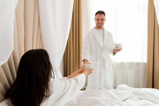 Man bringing coffee to his girlfriend lying in bed