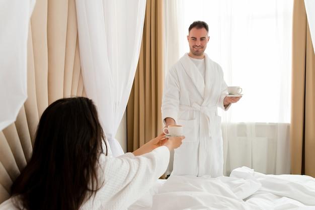 Мужчина приносит кофе своей девушке, лежащей в постели