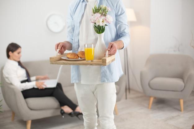 彼の妻の食べ物をもたらす男。フードトレイを持って男の写真をトリミングしました。その上に朝食用食品のトレイを保持している白い服を着ている男性のショットをトリミングしました。背景をぼかした写真のソファに座っている女性。
