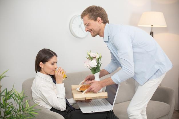 Мужчина приносит жене еду. леди выпивала, что ее парень принес ей. красивая женщина пьет апельсиновый сок с подноса еды, который ее муж держит к ней