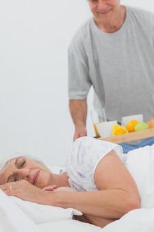 Man bringing sleeping wife breakfast in bed