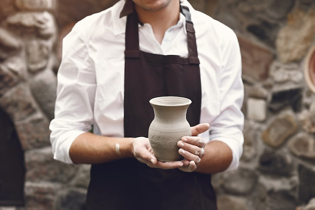 Man in a brown apron standing with a vase