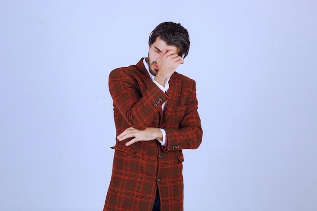 L'uomo in giacca marrone si sente male o si ammala.