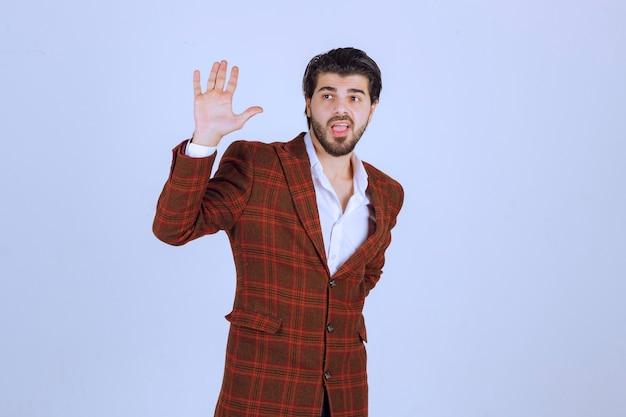 Uomo in giacca sportiva marrone che saluta qualcuno. Foto Gratuite