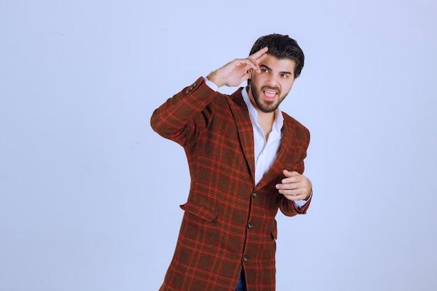 Uomo in giacca sportiva marrone che saluta qualcuno.