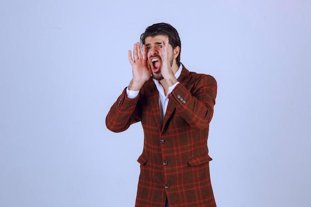 Man in brown blazer having speech with wide opening his hands.