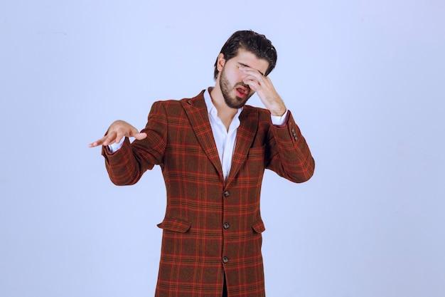 L'uomo in giacca marrone sembra confuso e cerca di spiegarsi.