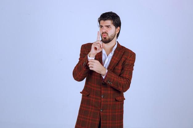 Uomo in giacca sportiva marrone che fa segno di silenzio.
