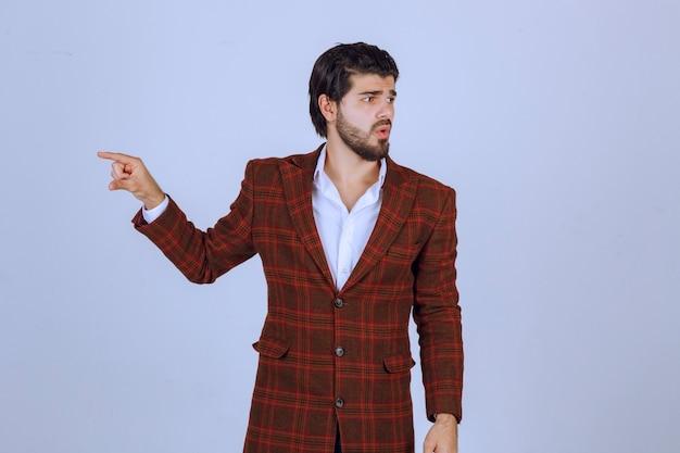 Uomo in giacca sportiva marrone che punta a qualcosa a sinistra e ne parla.