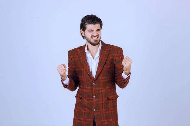 L'uomo in giacca marrone mostra i pugni e si sente molto motivato.