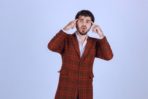 Uomo in giacca sportiva marrone pensando e pianificando. Foto Gratuite
