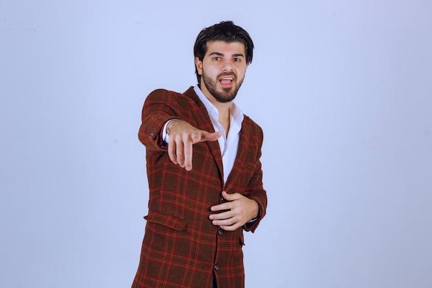 Uomo in giacca a quadri marrone che punta a qualcuno davanti.