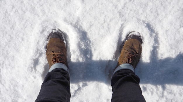 Man brown leather suede boot shoe on the white snow.