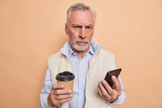 男は現代のスマートフォンでワイヤレスインターネットを閲覧します飲み物カフェイン芳香族飲料エレガントな服を着て厳格な表現で見えます