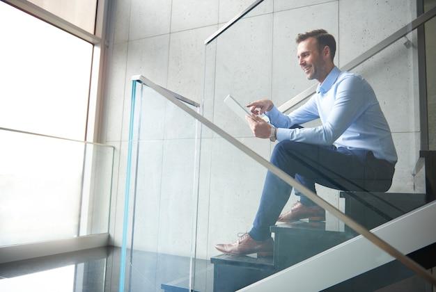 Человек просматривает цифровой планшет в офисе