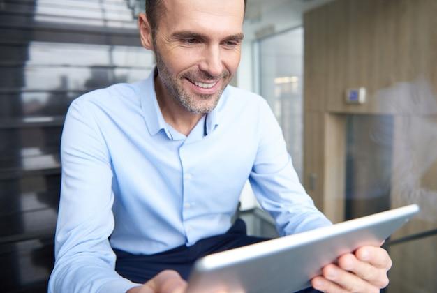 オフィスでデジタルタブレットを閲覧する男