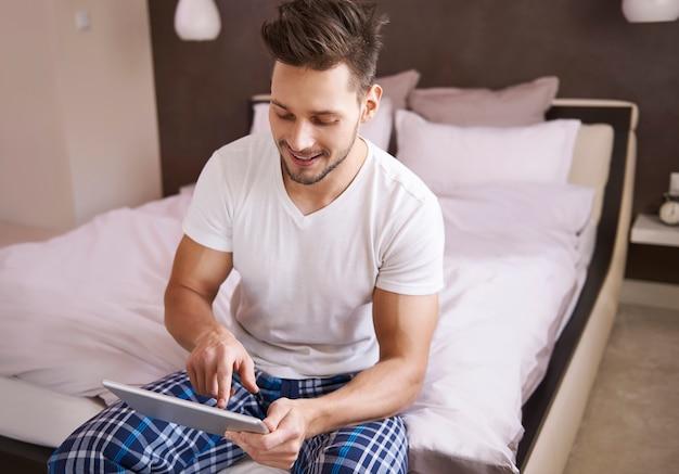 寝室でインターネットページを閲覧している男性