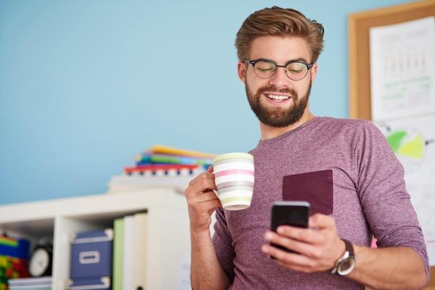 携帯電話を閲覧し、コーヒーを飲む男
