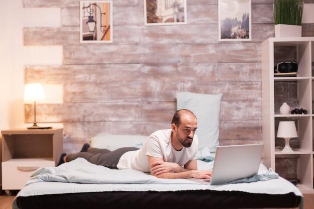 잠옷을 입고 침대에서 밤에 노트북을 검색하는 남자.