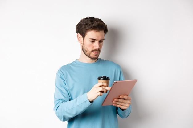 디지털 태블릿에서 온라인으로 검색하고 종이컵으로 커피를 마시고 흰색 배경 위에 서 있는 남자. 복사 공간