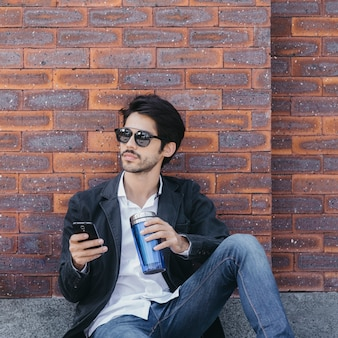 Man browsing smartphone and drinking near wall
