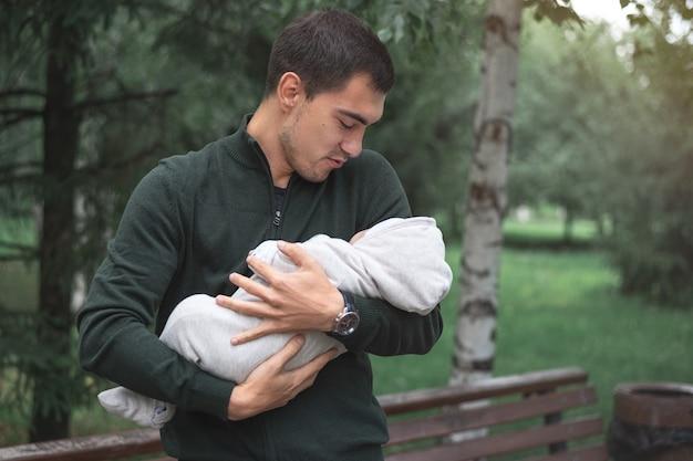 공원에서 팔에 갓 태어난 아기와 함께 갈색 머리 남자