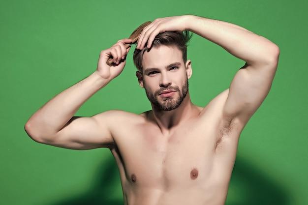 男は緑の背景にヘアブラシで髪を磨きます。セクシーな胴体、散髪の男。美容、身だしなみ、衛生。健康、フィットネス、ボディケア。ヘアケア、ヘアスタイルのコンセプト。